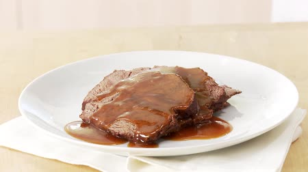 beef dishes : Beef pot roast being served with gravy