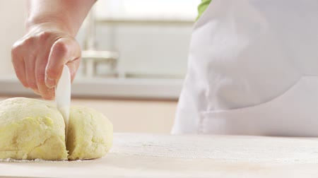 мучной : A work surface being sprinkled with flour and potato dough being rolled