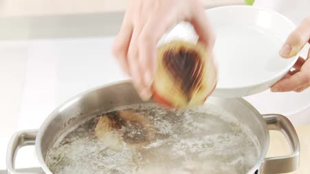 basic steps : Roasted onion halves being added to a pot of soup