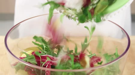 basic steps : Mixed leaf salad being placed in a bowl Stock Footage