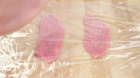 veal escalope : Veal escalopes being tenderized in cling film