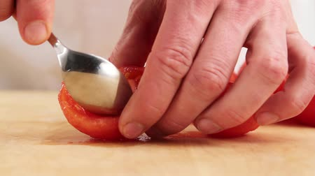 being removed : A peeled tomato being quartered and deseeded