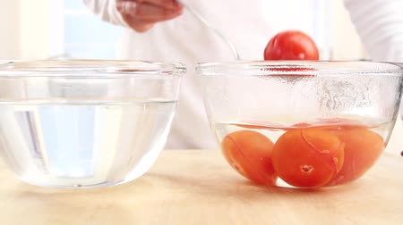 branquear : Tomatoes being removed from a bowl of hot water and placed into a bowl of cold water