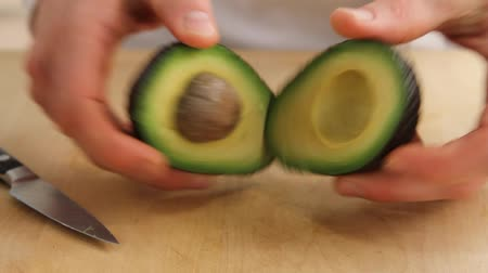 avokado : An avocado being halved and peeled Stok Video