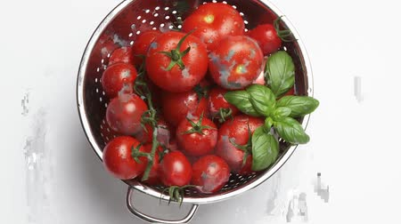 outlinable : Tomatoes and basil leaves in a colander Stock Footage