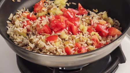 frypan : Rice being fried with diced aubergine and tomatoes