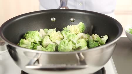 basic technique : Garlic, broccoli and spring onions being added to a pan