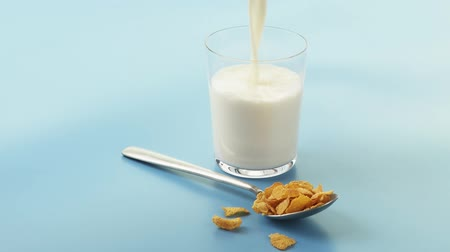 outlinable : A spoonful of cornflakes and a glass of milk being poured