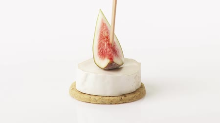 outlinable : Soft cheese and fig on cocktail stick on cracker Stock Footage
