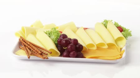 sliced cheeses : Cheese platter with grapes and salted sticks