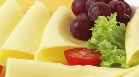 being cut up : Cheese platter with grapes and salted sticks