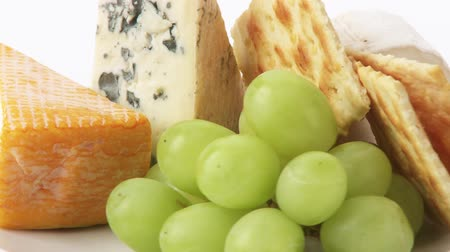 pieces of cheese : Cheese plate with crackers, grapes and walnuts