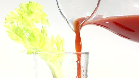 poured out : Pouring tomato juice into a glass with a stick of celery Stock Footage