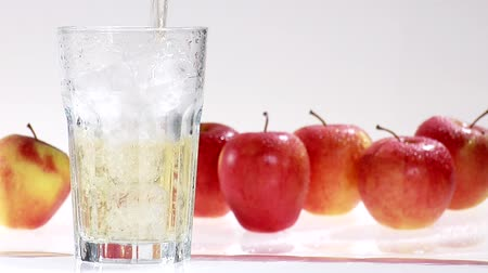pour out : Pouring apple juice into a glass of ice cubes
