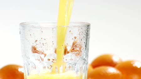 poured out : Pouring orange juice into a chilled glass (close-up)