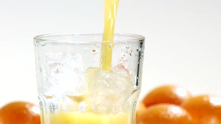 poured out : Pouring orange juice into a glass of ice cubes