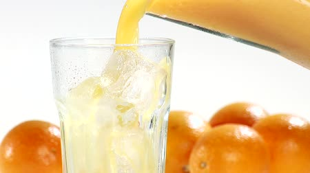 pour out : Pouring orange juice into a glass of ice cubes