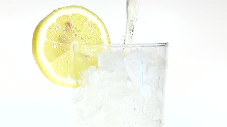 poured out : Pouring apple juice into glass of crushed ice with slice of lemon