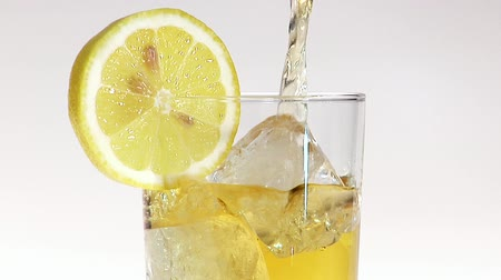 outlinable : Pouring apple juice into glass of ice cubes with slice of lemon