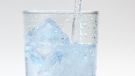 крупные планы : Pouring mineral water into a glass of ice cubes (close-up)
