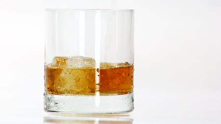 poured out : Pouring whisky into a glass with one ice cube