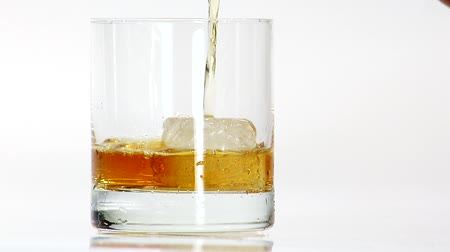 viski : Pouring whisky into a glass with one ice cube