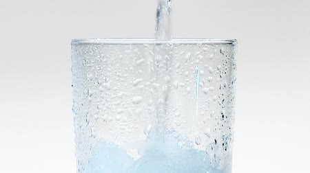 woda mineralna : Pouring water into a glass of crushed ice (close-up) Wideo