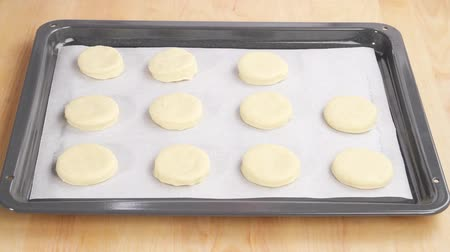 scones : Pastry circles (for scones) being placed on a baking tray lined with grease-proof paper