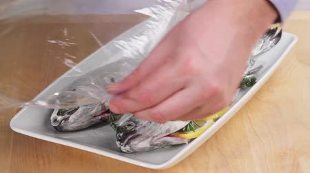 cling film : Prepared herb trout being covered with cling film