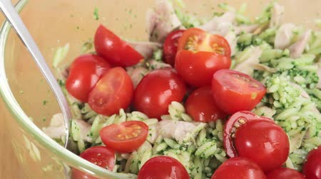 poulet : Cherry tomatoes being added to chicken and orzo pasta salad Stock Footage