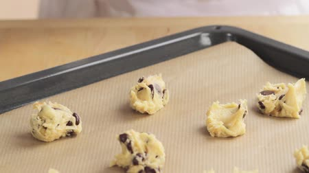 origens : Balls of chocolate chip dough being placed on a baking tray