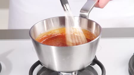 origens : Boiling barbecue sauce being stirred and then removed from the heat