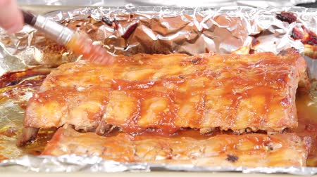 folyo : Spare ribs being grilled and brushed with marinade Stok Video