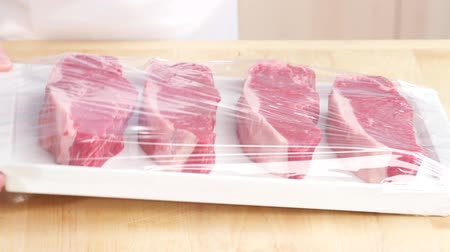 clingfilm : Cling film being removed from New York strip steaks