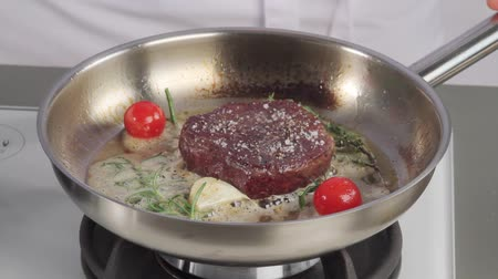 common salt : A fillet steak being season and aromatised with herbs, garlic and tomatoes