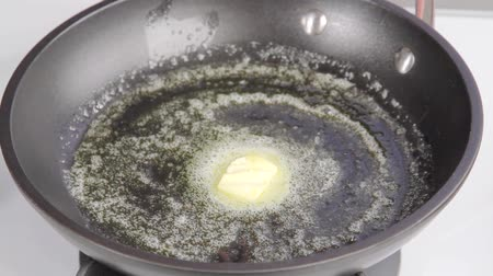 vaj : A piece of butter being melted in a pan Stock mozgókép
