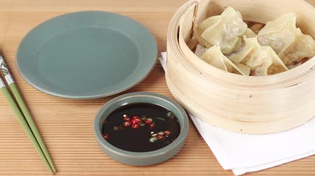 pastry purse : Dim sum in a bamboo basket and soy and chilli sauce Stock Footage