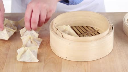 pastry purse : Dim sum being made: Stuffed pastry parcels being place in a bamboo basket