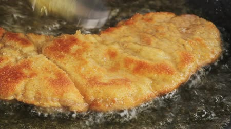 schabowy : Frying Wiener Schnitzel in a pan