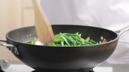 warzywa : Mixing spring onions with other vegetables in a wok