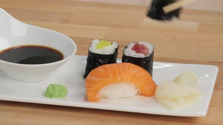 specialties : Picking up maki sushi with chopsticks and dipping in soy sauce