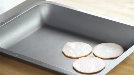 origens : Slices of ham being placed in a preheated roasting tin Vídeos