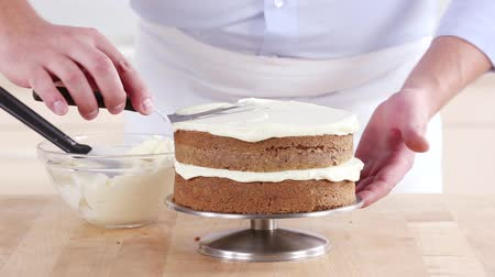 creams : A carrot cake being spread with cream cheese creme