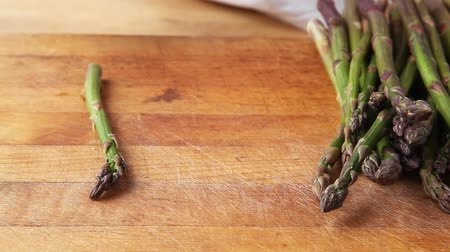 konec : The woody end being broken off green asparagus
