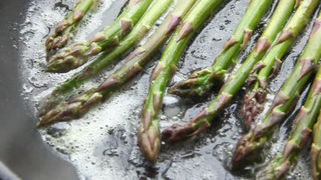 frypan : Green asparagus being fried in a pan of butter