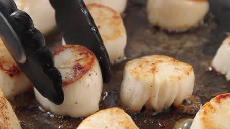 Removing fried scallops from a pan