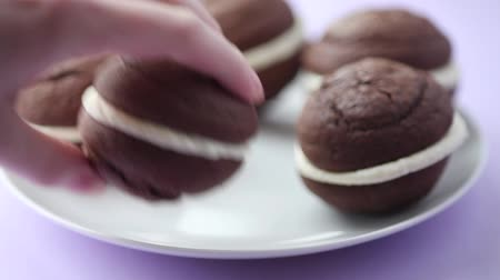 specialties : A hand taking a chocolate whoopie pie from a plate Stock Footage