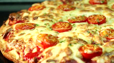 A pizza topped with mozzarella and cherry tomatoes, baking in the oven (close-up) Vídeos