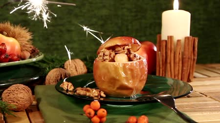 A baked apple on a table decorated for Christmas, with a sparkler