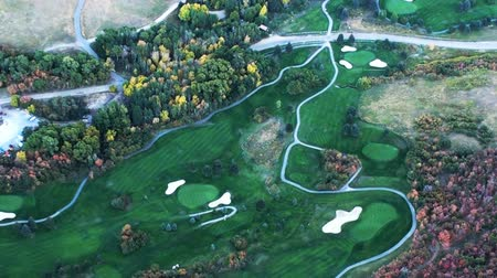 тройник : Aerial shot of golf course. Grass is freshly cut and green. Golf course has pools and colorful trees. Pathways for golf carts are visible. Filmed during the day. Стоковые видеозаписи
